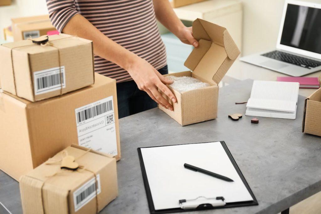 Schreibtisch mit braunem Paket das von einem Menschen gepackt wird, da es bald Verschickt wird